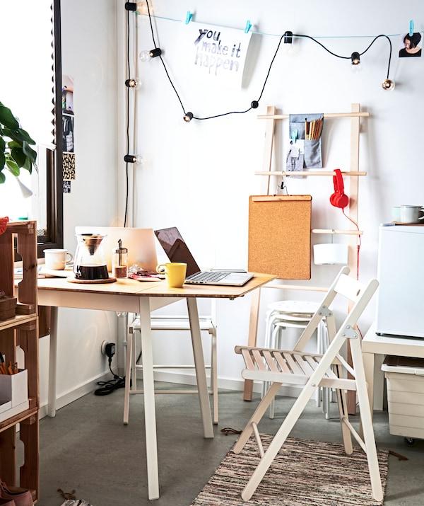 房间的一角摆放着一张桌子,桌子一端对着墙,四周是折椅、备用凳子和各种储物件。