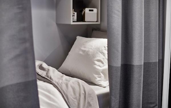 房间隔断帘后放着一张床。