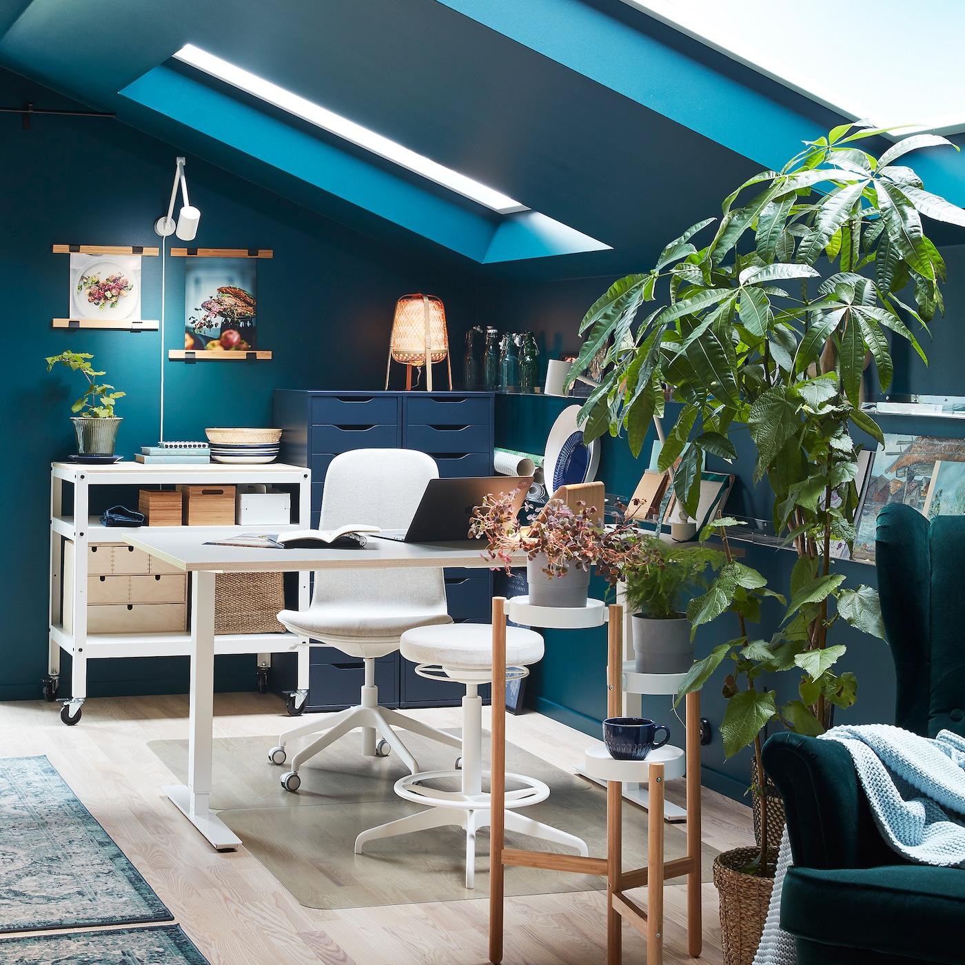 房间里摆放着书桌、白色转椅和椅凳、绿色植物和植物架,以及绿色靠背椅。