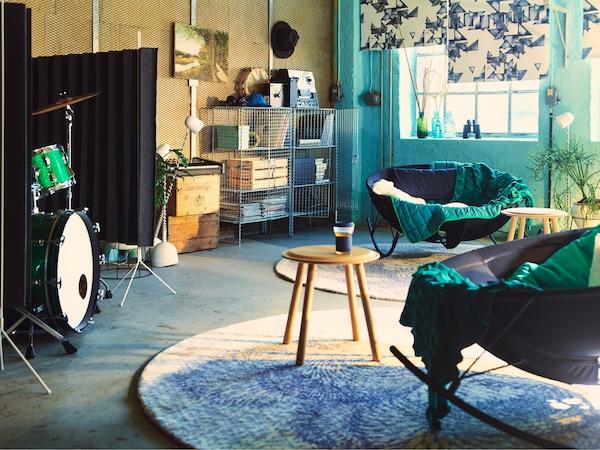 房间里有两张圆形黑色现代摇椅,上面带有绿色休闲毯,以及两张山毛榉木圆边桌。背景中有两个装满了音乐杂志和老唱片的镀锌钢储物单元。