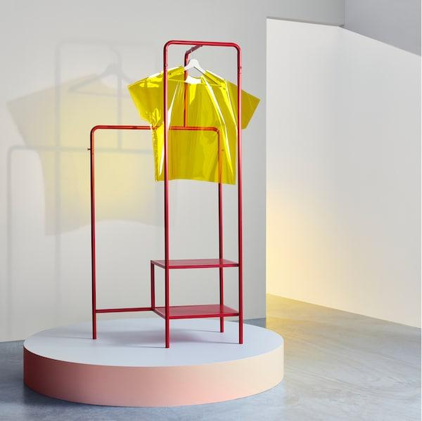 房间里有一个 NIKKEBY 尼克比 红色晒衣架,上面有一件用衣架挂着的黄色衣服。