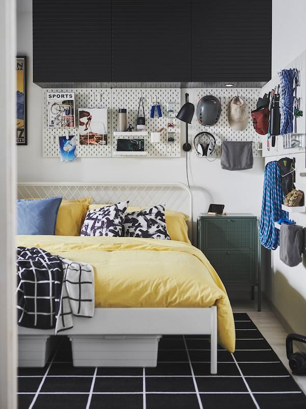 房间里有一张NESTTUN 奈斯顿 床,墙壁上的SKÅDIS 斯考迪斯 洞洞板上放着攀崖设备和充满青春气息的各种杂物配件。