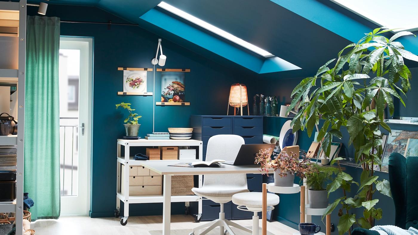 房间里有一张书桌、一张转椅和一张白色的坐/站两用式支撑椅,还有一个摆放着绿植的植物架。