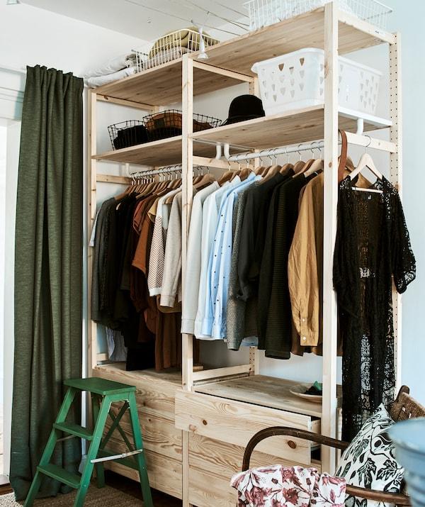 房间配有高高的木制带抽屉衣物储物单元、挂衣杆和储物盒搁板,角落里放着一张绿色踏脚凳。
