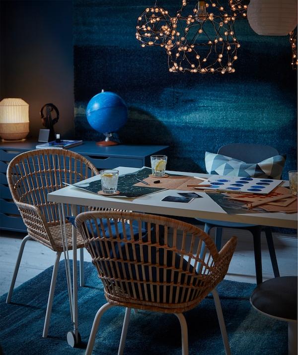 放有饮料和星图的桌子,柳条风格椅子,上方悬挂LED照明设备,地板和墙上饰有 SÖNDERÖD 桑德罗 地毯。