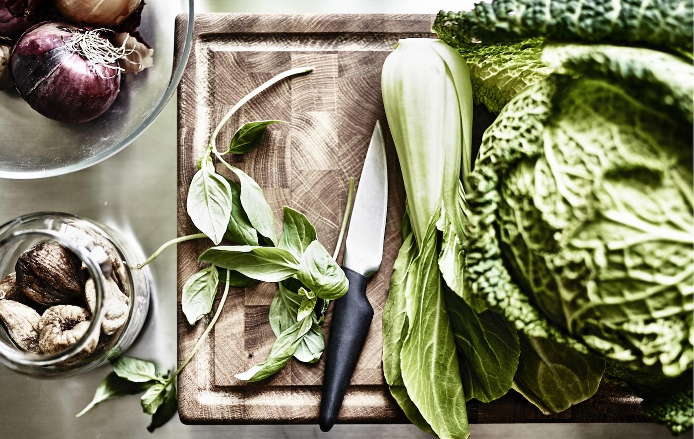 放在木质砧板上的绿色蔬菜和叶子。