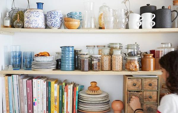 放在三块木质搁板上的厨具、书和干燥食材罐。