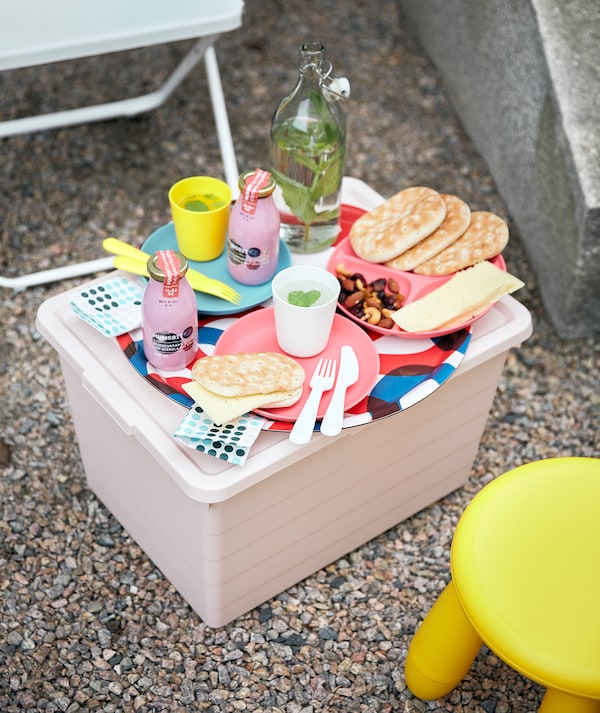 FEJAN 菲阳 椅子和 MAMMUT 玛莫特 凳子中间有一个粉色的 SOCKERBIT 索克比 储物盒充当小桌子,上面摆放着 HEROISK 希罗斯 餐具。