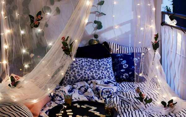封闭式阳台上摆放着一张宽大的床,蚊帐上饰有花朵和LED灯串,托盘上放着饮料和游戏用品。