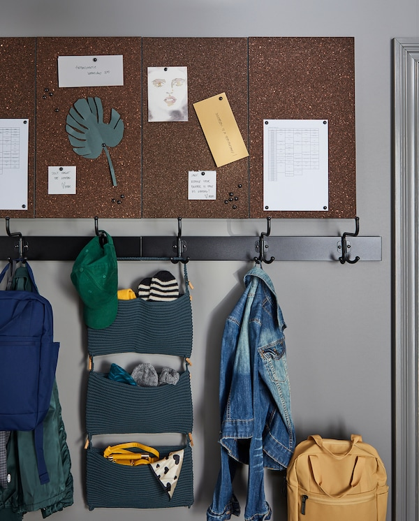 Four dark brown, wall-mounted SVENSÅS memo boards with pins with postcards, schedules and notes.