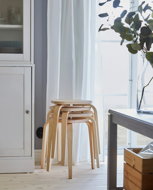 Four KYRRE stools in birch are stacked by a window, and they provide extra seating by a dining table when it's extended.