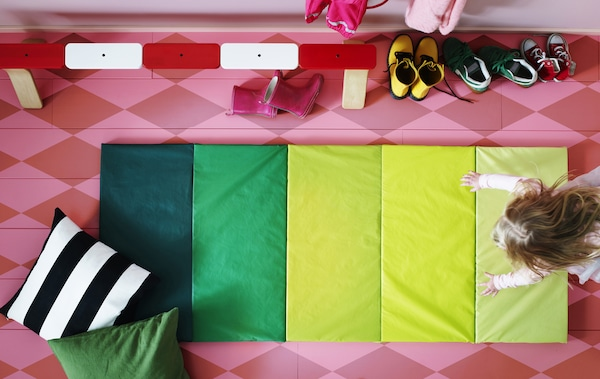 俯视图:粉色的地板上铺着一张绿色的条纹儿童游戏垫,一个孩子正在上面玩。