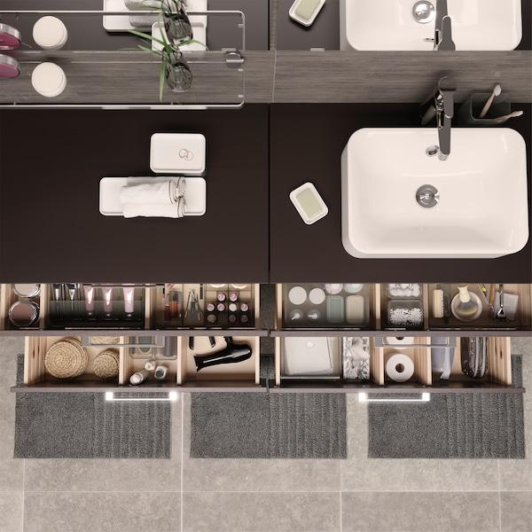 俯视图:四个打开的浴室抽屉,里面的物品整齐有序地收纳在带隔层的透明储物盒内。