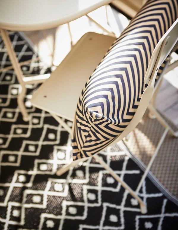 俯视图:椅子上放着黑白图案的靠垫,地板上铺着黑白相间的地毯。