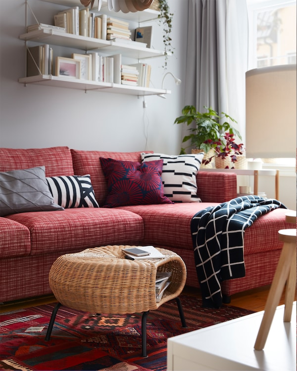 GAMLEHULT rattan footstool with storage on a red patterned rug, a red sofa, white wall-mounted shelves and a checkered throw.
