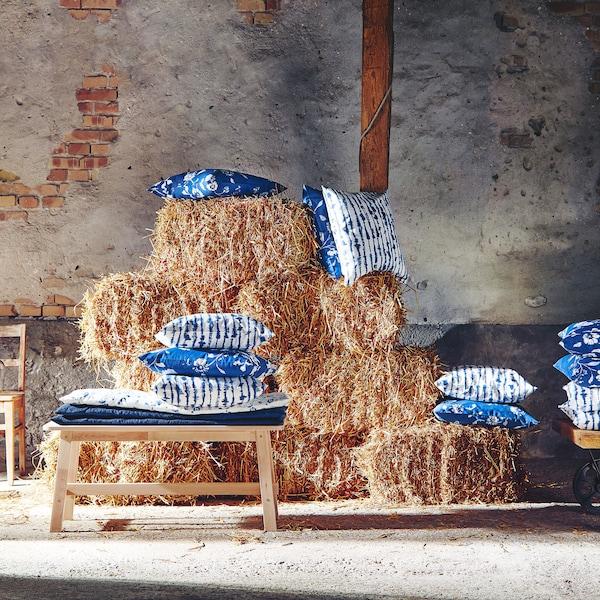 干草堆上展示着饰有花朵和印染图案的方形 BLÅGRAN 布洛格朗 和 STRIMSPORRE 斯特里普瑞 蓝白色垫套。