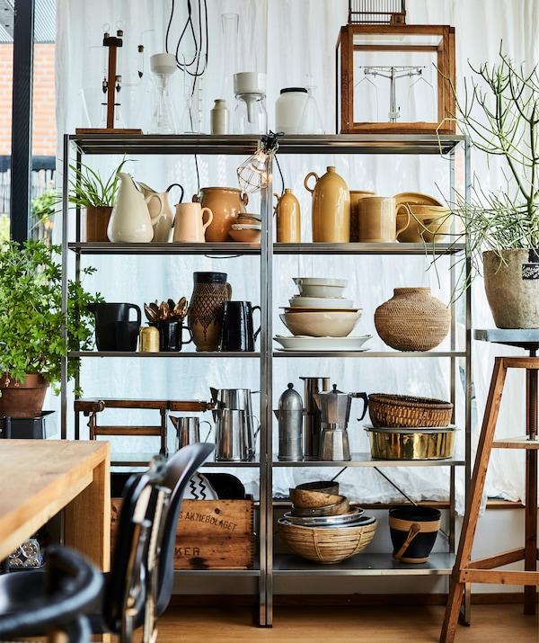 高高的金属搁架单元上陈列着陶瓷和厨具。
