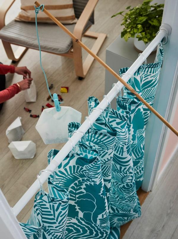 GATKAMOMILL 佳卡默米 浴帘挂在门口。玩具鱼竿跨帘而架,钓线上挂着一袋糖果。