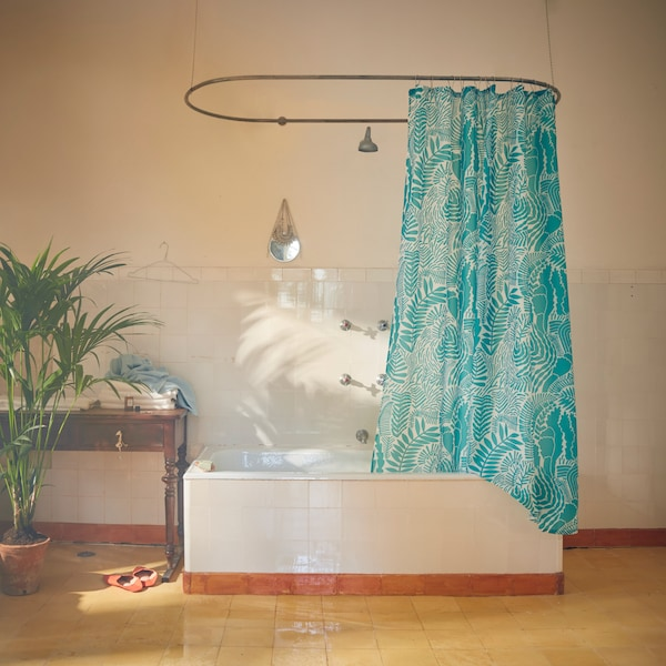 GATKAMOMILL shower curtain with a leafy pattern in turquoise and white hanging by a bathtub in a light-coloured bathroom.