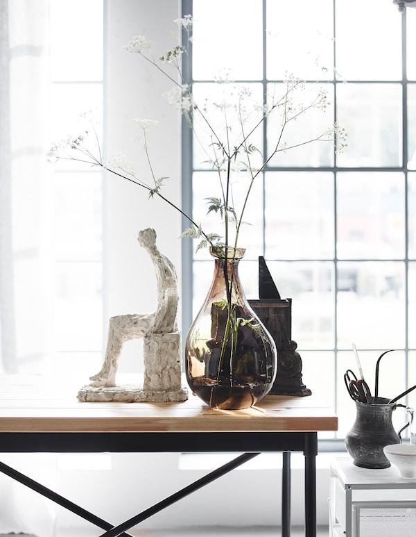 个人物品和插有精致小花的花瓶可为工业风书桌增添柔和感。