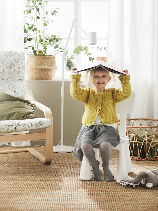 Girl playfully using an open book for a hat sits smiling on a white MAMMUT children's chair, placed next to a POÄNG armchair.