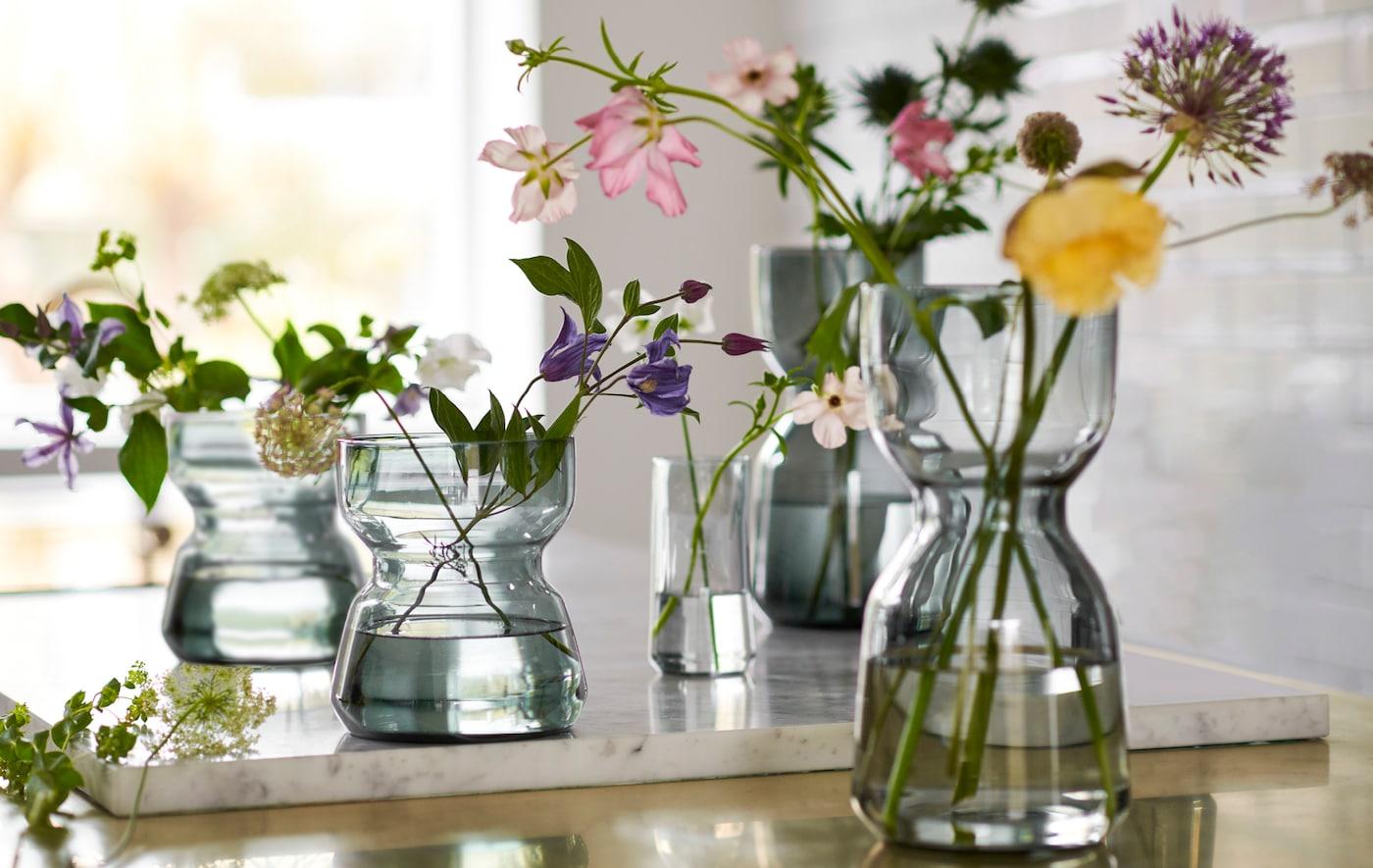 工作台上放着几个插着鲜花的 OMTÄNKSAM 沃姆安克萨姆 玻璃花瓶,瓶身采用别具一格的设计,便于抓握。