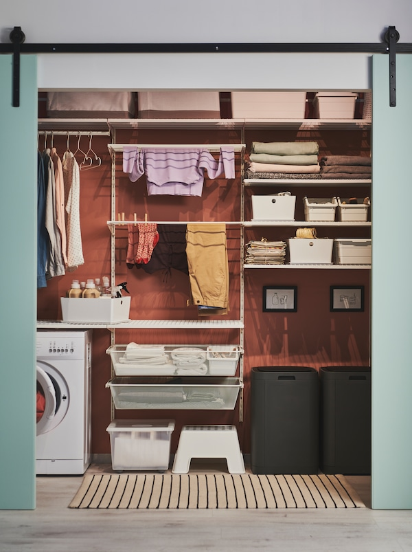 Green doors slid open to reveal a wall arranged for laundry, including GIGANTISK bins, BOAXEL shelving and a washing machine.