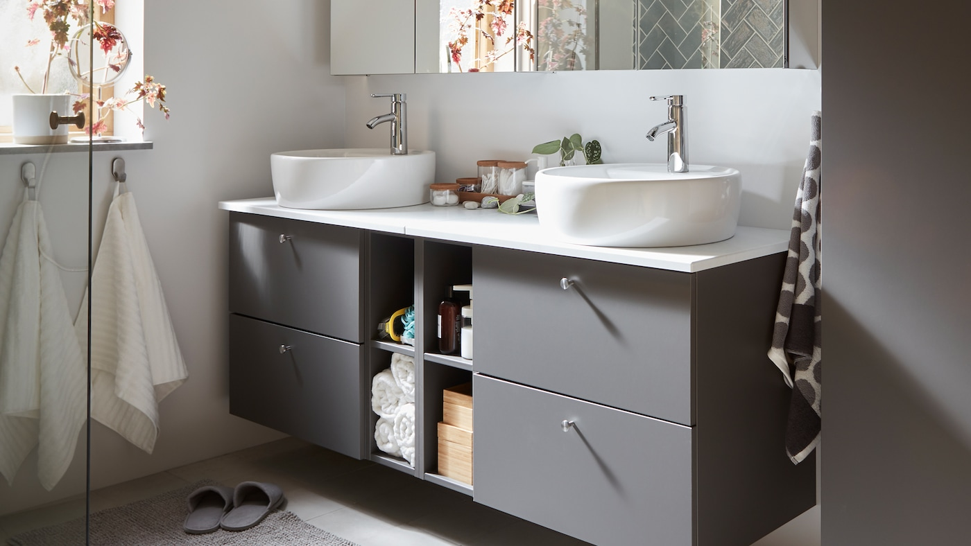 Grey GODMORGON/TOLKEN bathroom furniture with four drawers for hidden storage and four compartments for open storage.