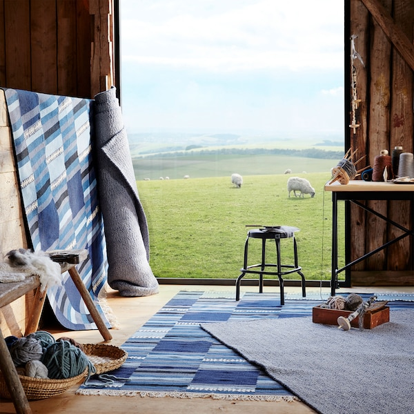 谷仓地板上紧靠着墙壁的位置展示着 LOVRUP 勒伍拉 羊毛和20%棉混纺地毯,以及蓝色渐变色调的 TRANGET 特朗格特 羊毛地毯。