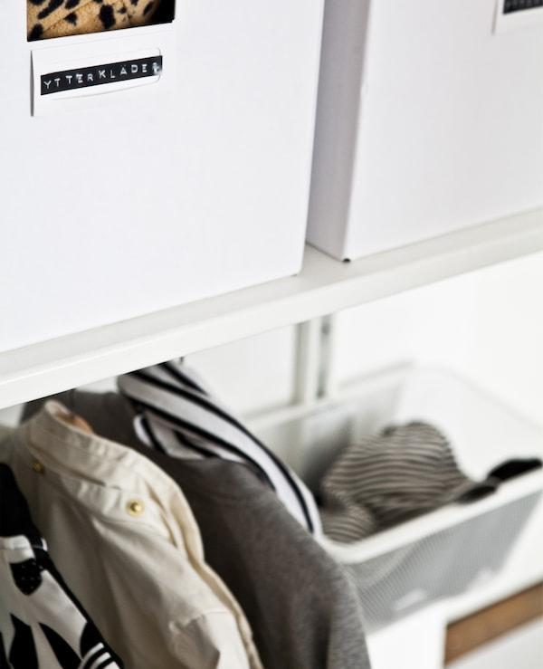 挂杆上方的搁架上摆放着带标签的白色储物盒。