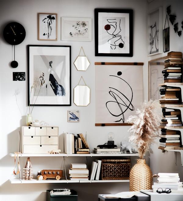 挂满画框的墙面、储物盒、书籍、挂钟、玩具和花瓶均为白色、黑色和褐色色调。