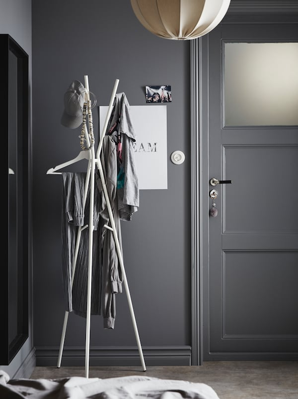 Hallway area in a grey colour scheme. By the front door stands an EKRAR hat and coat stand, holding various garments.