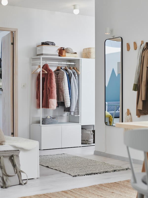 Hallway interior with spread out stations for hanging or storing clothes, including a white PLATSA wardrobe.