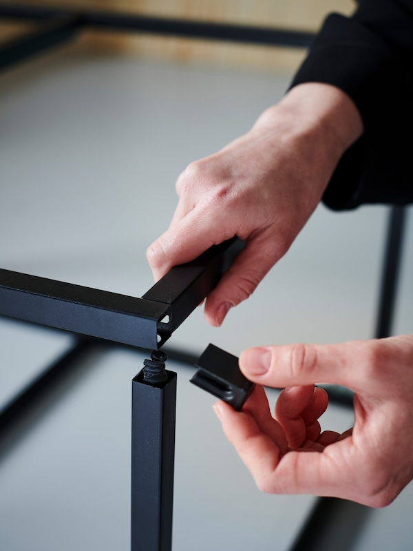 Hands assembling a black metal frame using a wedge dowel.