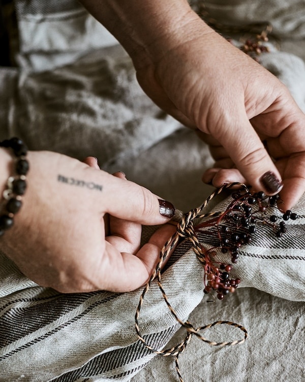Hands tying a decorative knot made from natural and black coloured twine and plum coloured wild berries round a napkin.