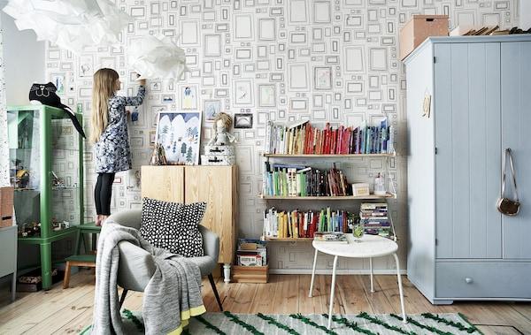 Hania在她的卧室里,房内摆放着彩色家具、绿色地毯和彩虹书架。