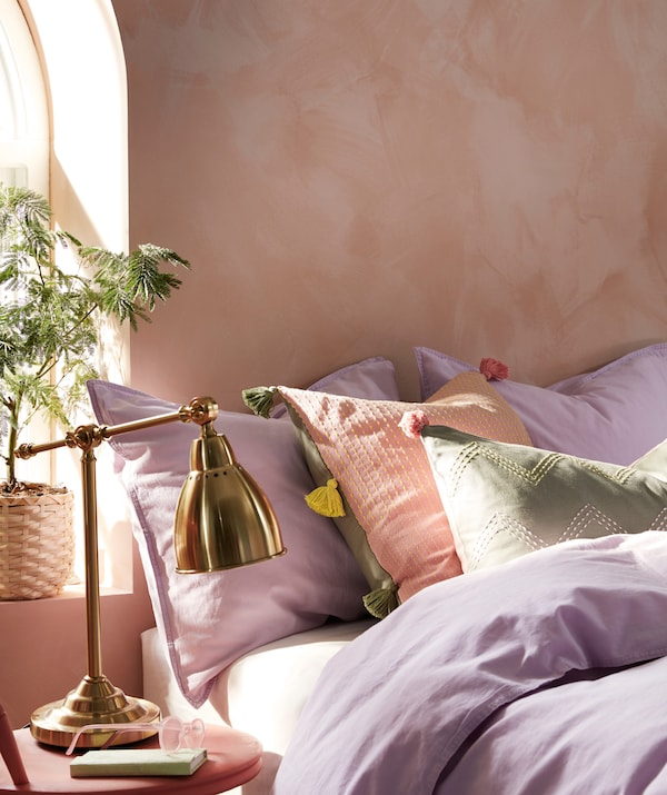 Haphazardly made, sunlit bed in which cushions with MOAKAJSA and KLARAFINA covers lie among pillows and bed linen.