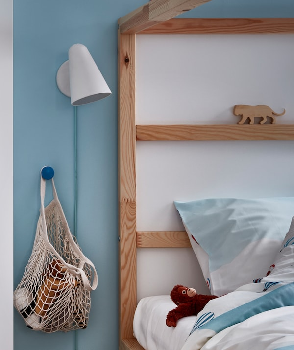Headboard end of a child's bed with a net bag of soft toys hangs on a knob bedside. Wall lamp, a soft toy by the pillow.