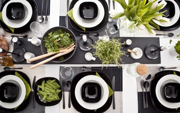 黑白色调的餐桌上摆放着亮眼的绿色植物、食品和餐巾。