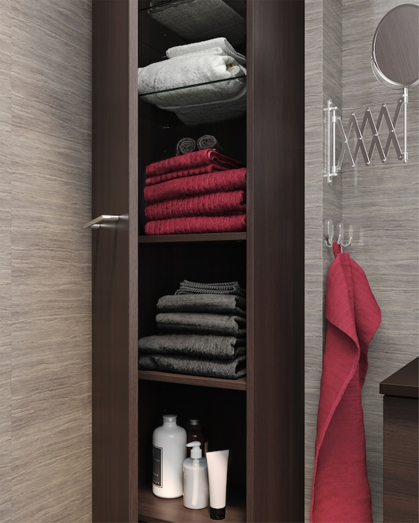 黑褐色高柜敞开着,内部储物空间充足,其玻璃以及木质搁板上可容纳毛巾、洗发液等物品。