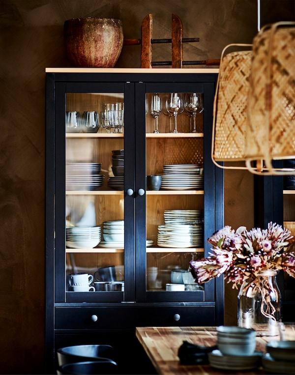 黑褐色HEMNES 汉尼斯 玻璃门柜内摆满玻璃酒杯和餐具,前面是一张摆放着花瓶的餐桌。