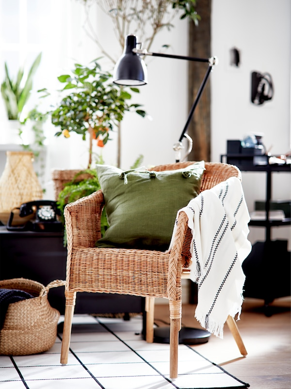 黑色、白色和绿色的客厅,摆放着大棵的植物、AGEN 爱格 藤制椅子和天然材料的装饰点缀。