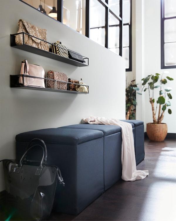 黑色储物脚凳,黑色搁板上放有包袋和绿色植物。