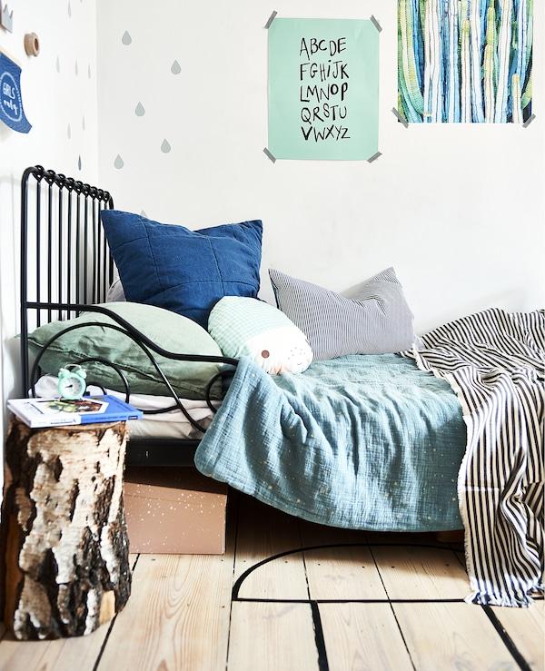 黑色床架上铺着绿色和蓝色的床上用品,墙上则贴着画。