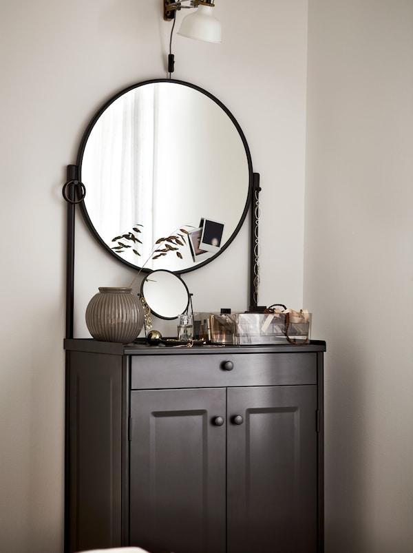 黑色的KORNSJÖ 康恩索 柜子,配一面圆形大镜子,上面摆放着各式装饰品,上方是一盏白色的灯。