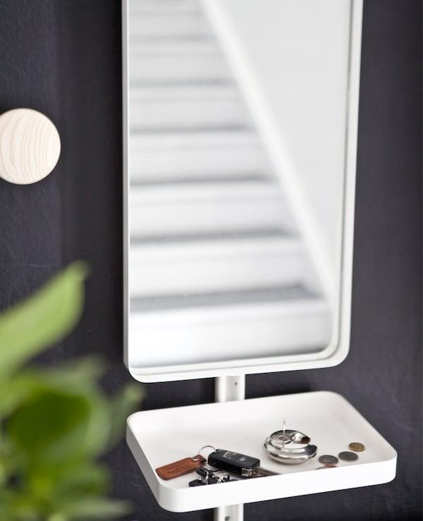 黑色墙壁上的镜子带有一张白色小托盘,里面放着钥匙和硬币。