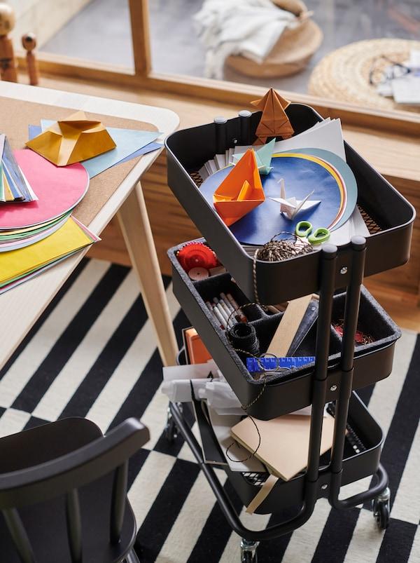 黑色RÅSKOG 拉斯克 推车上装满了手工艺术配件,旁边的桌面上铺满了彩色的纸张。