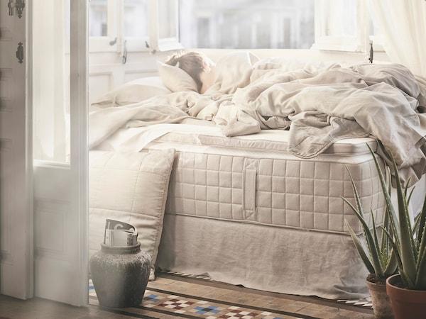 HIDRASUND 黑德拉桑 袋装弹簧床垫上放着白色/自然色床上用品和枕头。