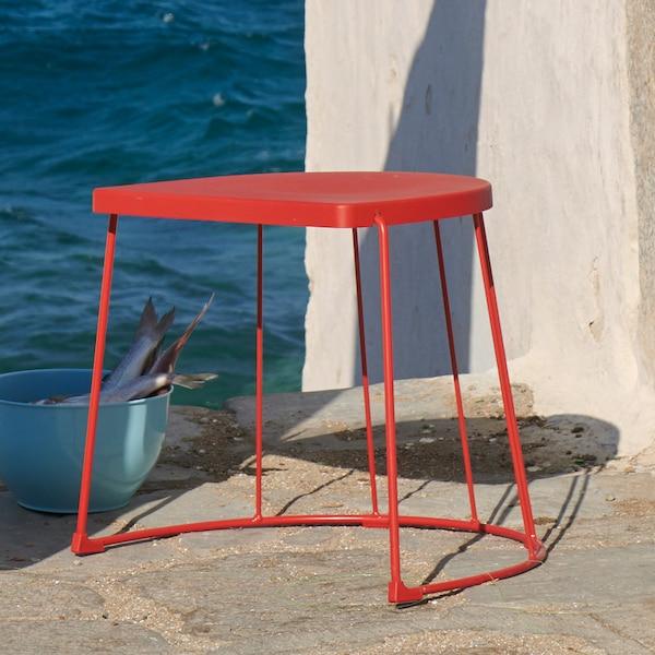 户外摆放着红色的 TRANARÖ 特拉纳瑞 凳子。