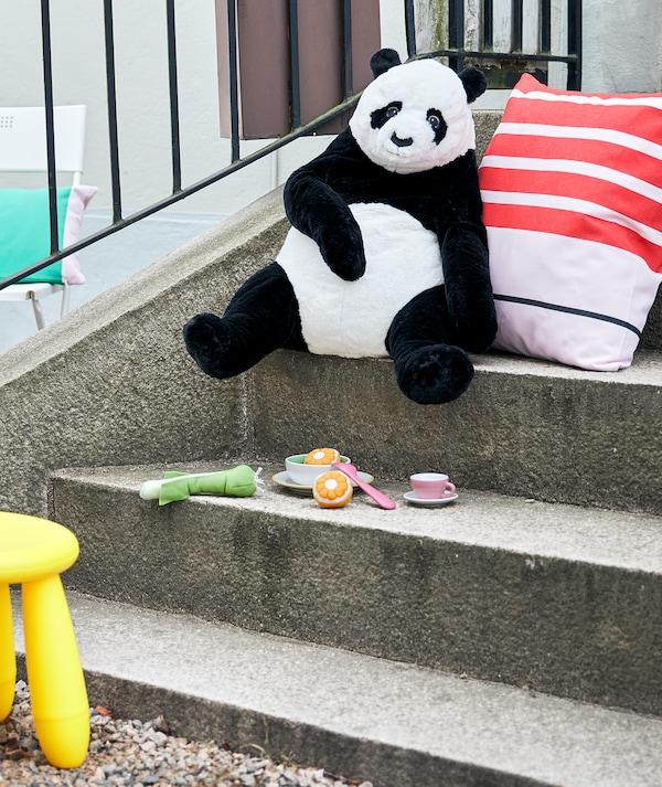 户外楼梯上,一只玩具熊猫靠在软垫上,就好像刚刚用下面的玩具餐具吃过饭一样。